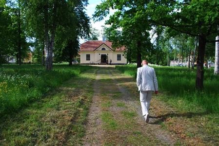 A man walking on the way to the house.