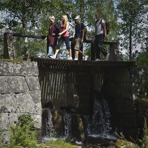 Four people walking on a bridge over water.