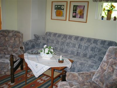 Living room, sofa, two arm chairs and a table.