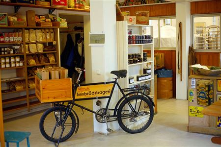 The store room with a bicycle in the middle, shelves with goods.