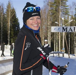 Woman on cross-country skis smiling.