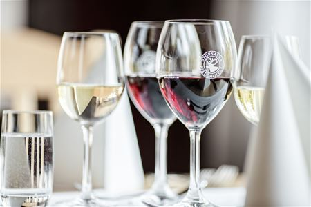 Several wine glasses with red and white wine.
