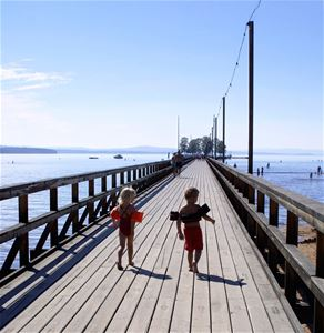 Two children are running on the bridge.