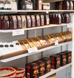 Shelves in the shop with chocolate cookies, apple juice, chocolate.