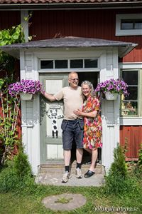 The owner couple stands at the entrance to the house.