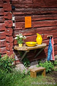 Shelf on a timber wall with a yellow jug and a bowl and towels hanging next to it. for washing hands.