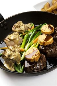 Black frying pan with meat pieces mushroom sauce vegetables and spice butter.