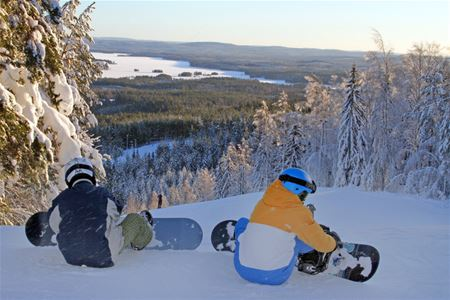 Two persons sitting down at the top of a ski slope, putting on their snowboards.