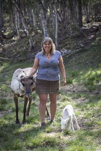 Owner with a reindeer and reindeer calf.