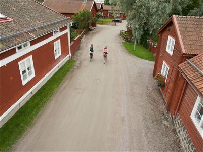 A couple cycling on a road between houses.
