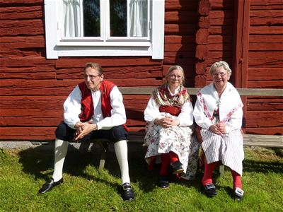 A man and two women sitting in front of a red house dressed in traditional clothes.