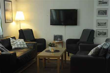 Welcoming common area with sofa, armchairs and tv.