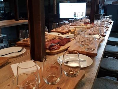 Long table with glass for beer tasting and plates where you can add different cheeses sausages and snacks.