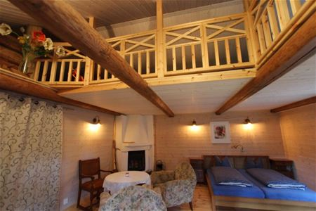Large room with double bed, open fire place and a loft.