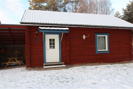Red log cabin with snow on the roof.