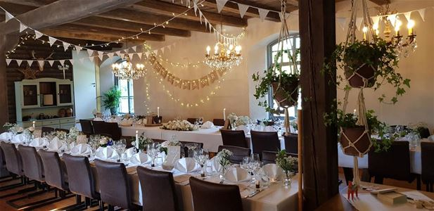 Beautiful wedding table set with white spring-shaped napkins, white summer flowers, chandeliers and crystal chandeliers.