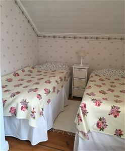 Bedroom with floral wallpaper and two single beds with a bedside table in between.