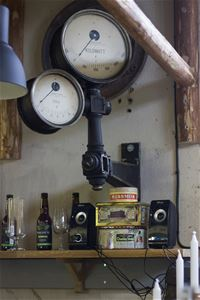 A wooden shelf with old tin cans, speakers, glasses and bottles.