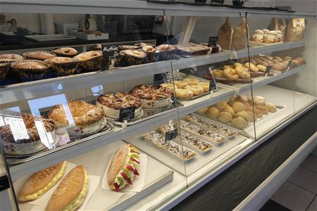 Pastries and cakes on display in a glass counter.