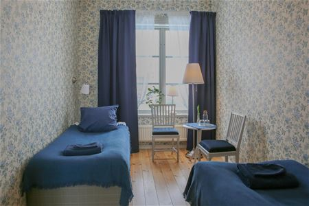 Two single beds in each corner of the room with blue bedspread and curtains.