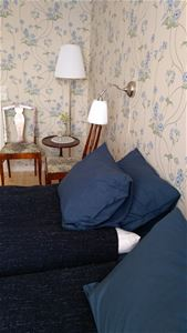 Blue pillows and two chairs and a little table and a lamp.