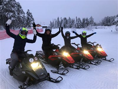 Four mini snowmobiles with drivers in winter landscape