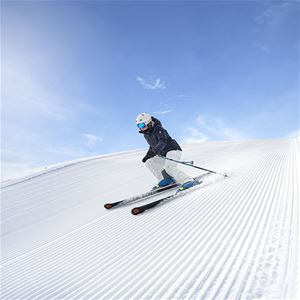 downhill skier on the piste, blue sky, blue sky