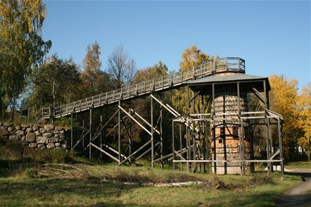 A blast furnace with a wooden bridge.