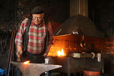A man forging in the smithy.
